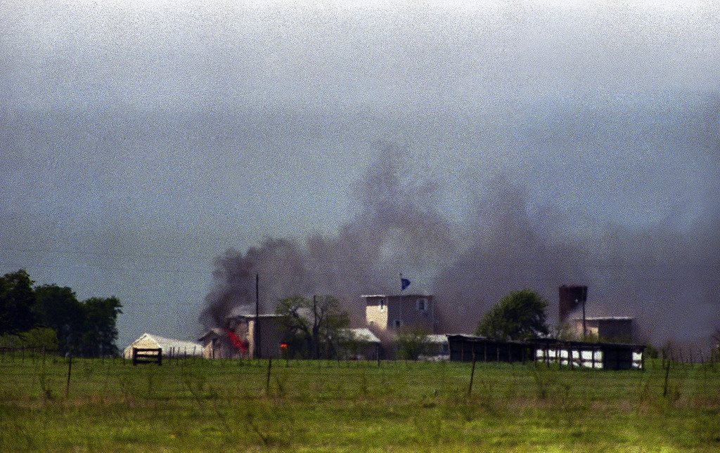 . Flames are seen in building to right of tower and smoke billows into sky as the fire first becomes visible at the Branch Davidian compound near Waco, Texas on Monday, April 19, 1993.  (AP Photo/Roberto Borea)
