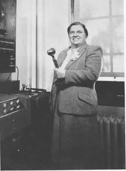 """The legendary Grace M. Durling aka """"Ma Durling"""" poised next to her evil weather machine or perhaps just the UHS vacuum tube powered intercom system complete with phonograph. Miss Durling was the principal of UHS from 1923 to 1956. She was also for a period of time the boys basketball, baseball and football coach as well as the coach for the girls basketball team. UTHS trustee Lore Ullrich recalls shaking in her boots as Ma Durling would march through the hallway."""