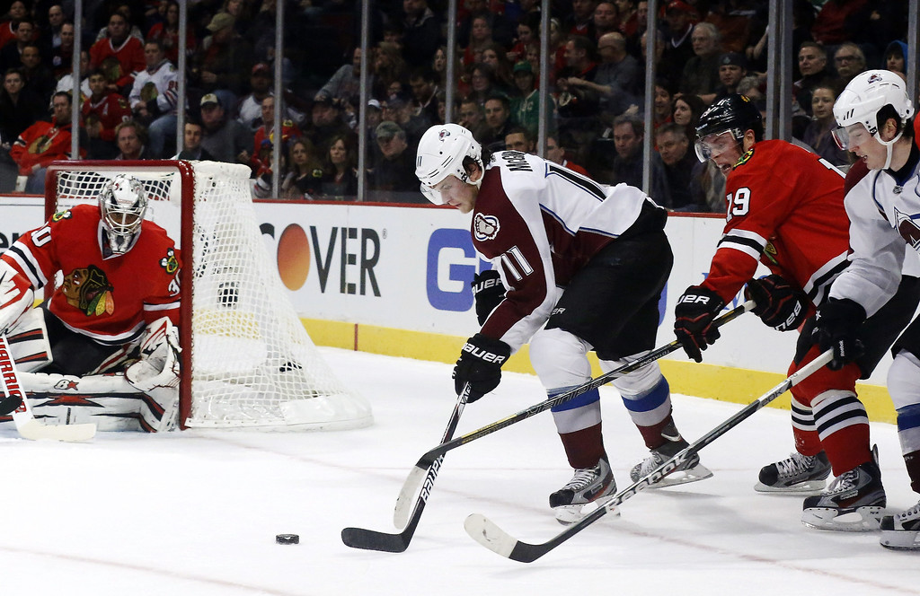 . Chicago Blackhawks center Jonathan Toews (19) keeps Colorado Avalanche left wing Jamie McGinn from getting a shot on Blackhawks goalie Ray Emery (30) during the first period of an NHL hockey game, Wednesday, March 6, 2013, in Chicago. (AP Photo/Charles Rex Arbogast)