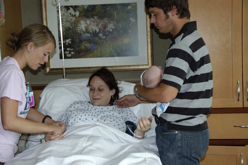 Nurse checking arm bands to make sure they are the parents of this little gal.