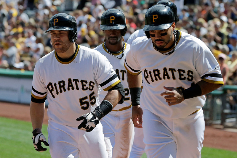 . Pittsburgh Pirates\' Russell Martin, left, returns to the dugout with teammates Pedro Alvarez, right, and Andrew McCutchen, who were on base for his  three-run home run off Colorado Rockies relief pitcher Manny Corpas (60) in fifth inning of an MLB National league baseball game in Pittsburgh Sunday, Aug. 4, 2013. (AP Photo/Gene J. Puskar)