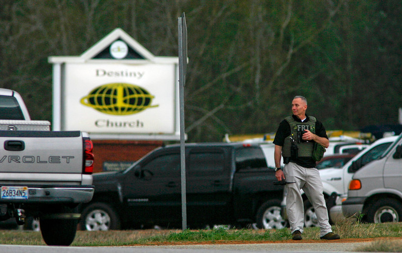 . An FBI official stands at a roadblock near Destiny Church, the scene of a shooting and hostage taking, in Midland City, Alabama, January 30, 2013. A gunman boarded an Alabama school bus ferrying children home from school on Tuesday and fatally shot the driver before fleeing with a young child and holing up in an underground bunker, Alabama media reported. Sheriff\'s officials confirmed that one person had been killed in a shooting involving a school bus in Alabama\'s Dale County but gave scant details other than to say that a child was present at the scene in Midland City. REUTERS/Phil Sears