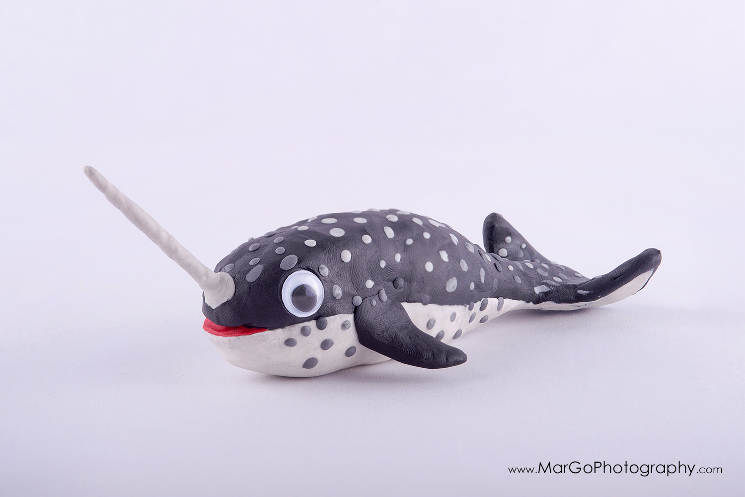 photography of grey clay narwhal on white background