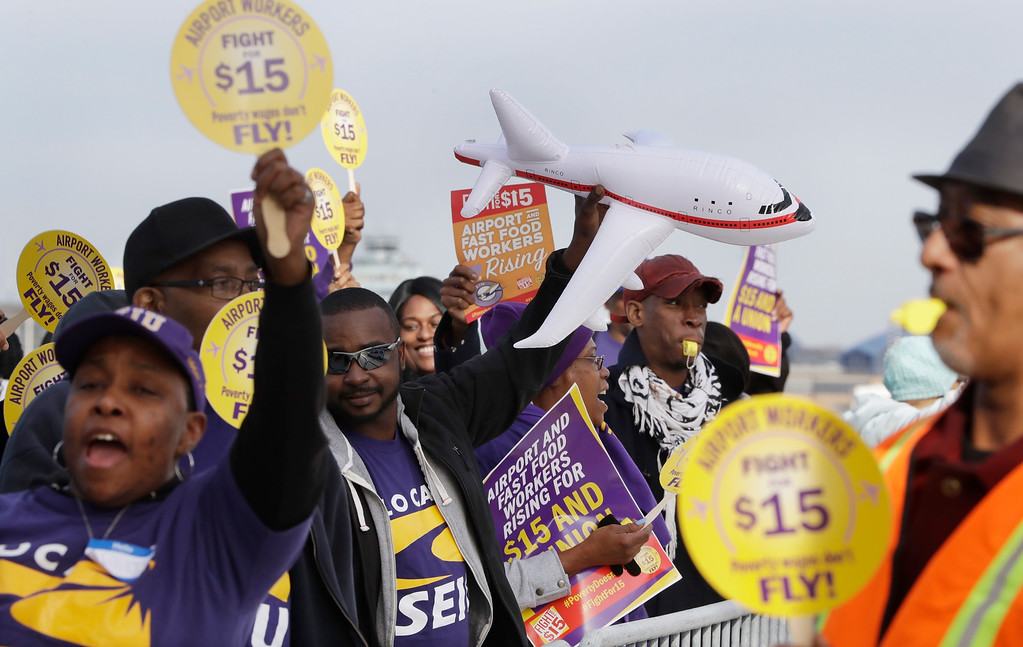 . SEIU Local 1 union members protest for an increase in the minimum wage, Tuesday, Nov. 29, 2016, at the Detroit Metropolitan Airport in Romulus, Mich. Fast-food restaurant and airport workers, as well as home and child-care workers rallied in cities including Chicago, Detroit, Houston, Los Angeles, Minneapolis and New York on Tuesday morning. In many cities the protesters blocked busy intersections. (AP Photo/Carlos Osorio)