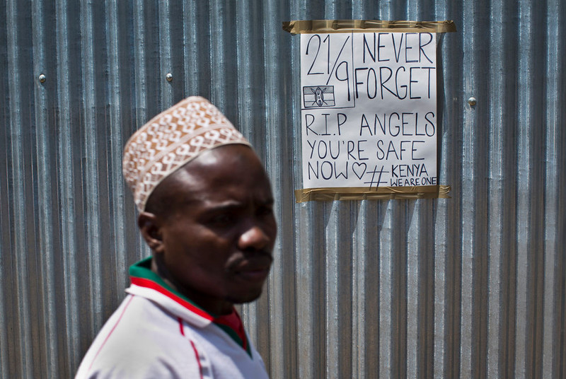 . A man walks past a sign put up in memory of the victims of the Westgate Mall attack, on a metal fence outside the still-closed mall in Nairobi, Kenya Sunday, Sept. 21, 2014. Kenya is marking one year since four gunmen stormed the upscale Westgate Mall in Nairobi, killing 67 people, and a memorial plaque with the names of the victims was unveiled at a popular forest on the edge of the city. (AP Photo/Ben Curtis)