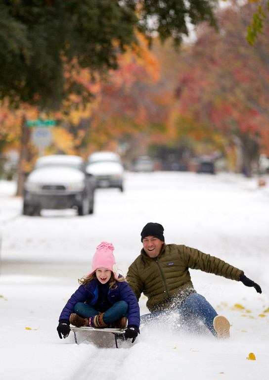 . Mark Vogel gives his daughter Parker, 7, a push on the sled he used when he was a kid on the icy streets in Fort Worth, Texas on Friday, Dec. 6, 2013. Winter storm and ice warnings are in effect through much of today for parts of six states in the Midwest, including Texas, Missouri, Illinois and Indiana. (AP Photo/The Fort Worth Star-Telegram, Joyce Marshall)