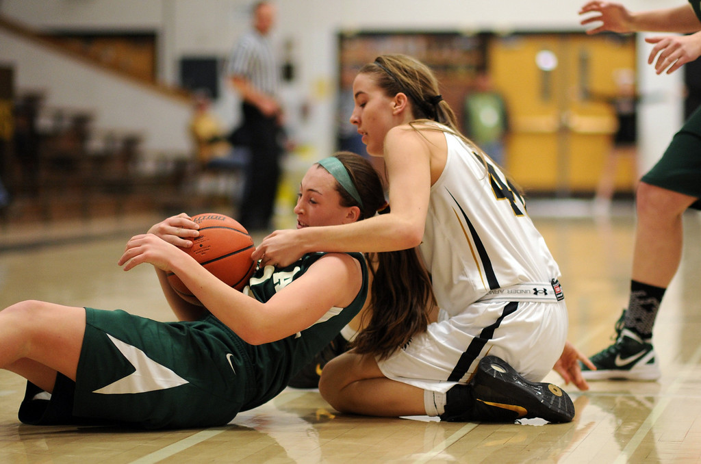. Arapahoe\'s Mikaela Moore, right, and Mountain Vista\'s Paige Keller are fighting for the free ball in the second half of the game at Arapahoe High School Gym onSaturday, Jan. 5, 2013, in Centennial, Colo. Arapahoe won 74-38. Hyoung Chang, The Denver Post