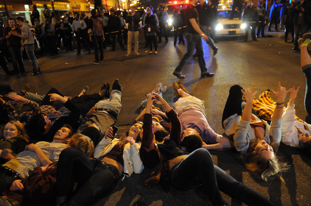 ". U of M fans take ""selfies\"" as they lie on the ground while Minneapolis police in riot gear, back, get into position to break up the crowd. (Pioneer Press: Sherri LaRose-Chiglo)"