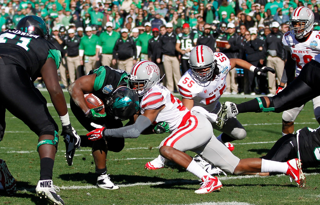 . North Texas running back Antoinne Jimmerson (22) scores a touchdown as UNLV defensive back Mike Horsey (32) is unable to prevent the score during the first half of the Heart of Dallas NCAA college football game, Wednesday, Jan. 1, 2014, in Dallas. (AP Photo/Mike Stone)
