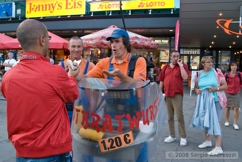 A nomade hot-dog seller is giving the last hot dog to a passer-by, in the background a man is performing cleaning operations :-)
