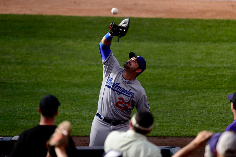 Description of . Adrian Gonzalez (23) of the Los Angeles Dodgers makes a catch as he nears the fans during the Dodgers' 10-8 win in Denver on Monday, September 2, 2013. The Colorado Rockies hosted the Los Angeles Dodgers at Coors Field. (Photo by AAron Ontiveroz/The Denver Post)