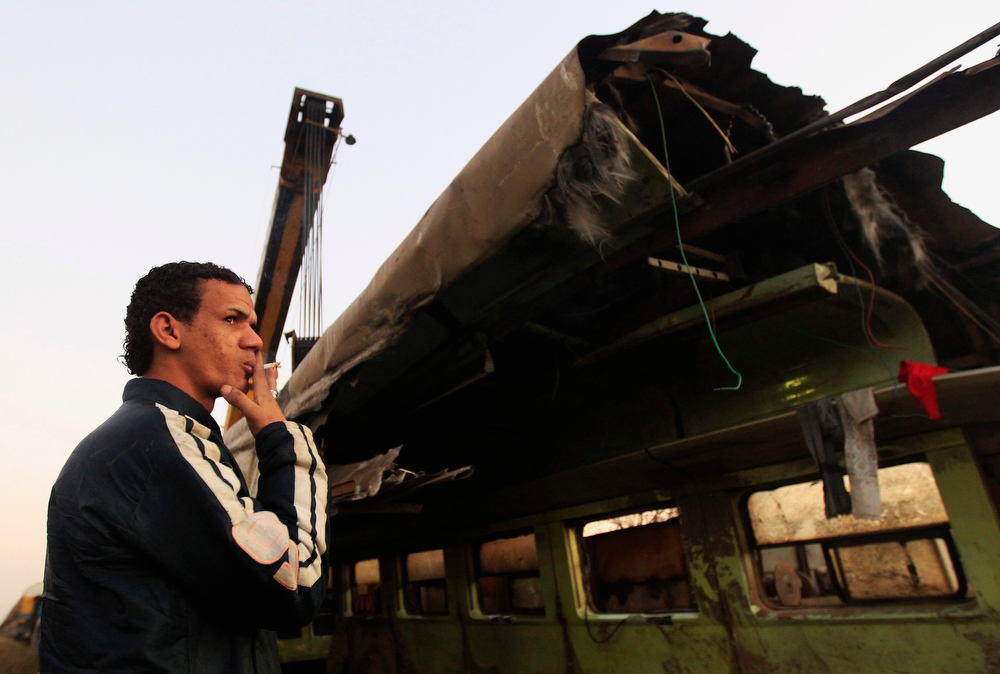 Description of . A man smokes beside the wreckage of a military train crash in the Giza neighbourhood of Badrashin, about 40 km (25 miles) west of Cairo, January 15, 2013. A military train carrying young recruits to an army camp derailed in a Cairo suburb on Tuesday, killing 19 people and injuring 107, Egypt's health ministry spokesman said.   REUTERS/Mohamed Abd El Ghany
