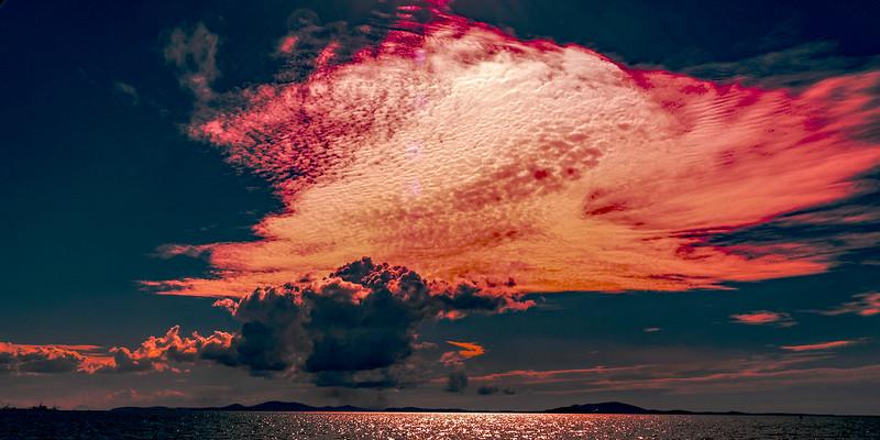 Red colored cirrocumulus cloud, sunset seascape.