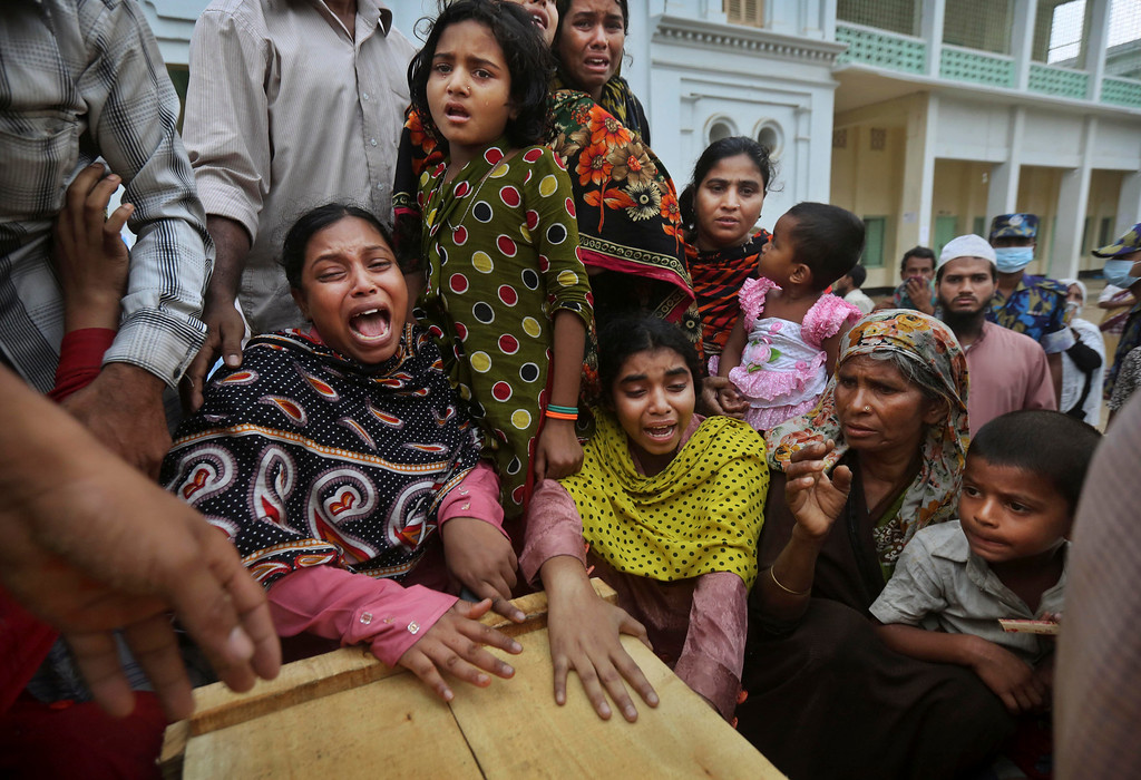 . Bangladeshi relatives of garment worker Mohammed Abdullah cry as they gather around his coffin after collecting his body at a makeshift morgue in a schoolyard near a building that collapsed Wednesday in Savar, near Dhaka, Bangladesh, Saturday, April 27, 2013. Police in Bangladesh arrested two owners of a garment factory in a shoddily-constructed building that collapsed this week, killing hundreds of people, as protests spread to a second city Saturday with hundreds of people throwing stones and setting fire to vehicles. (AP Photo/Kevin Frayer)