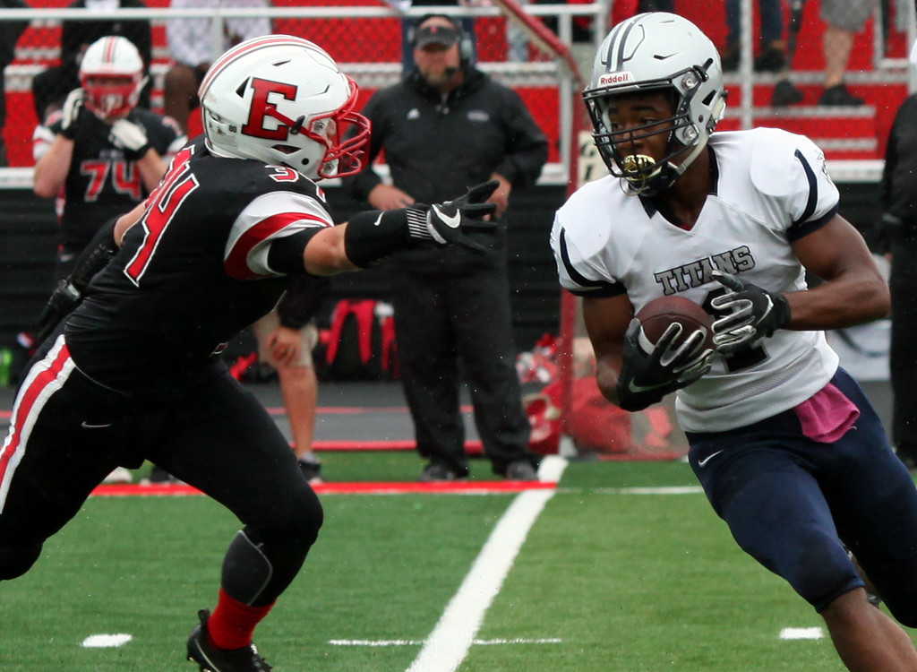 . Randy Meyers - The Morning Journal<br> Lorain\'s Tyshawn Lighty runs past Michael Knapp of Elyria on a reverse play during the first quarter on Sept. 8.