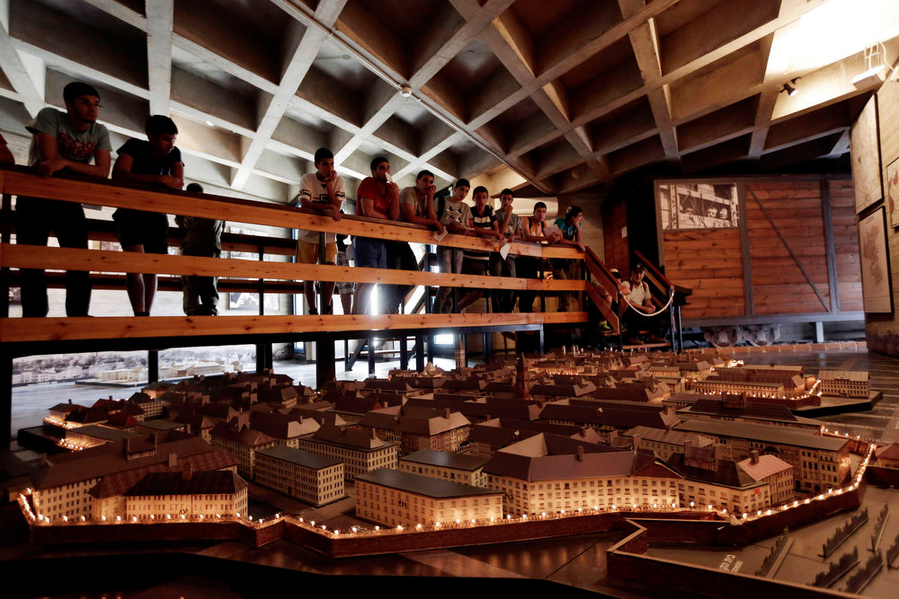 ". Israeli high school students look at a model of the Warsaw Ghetto at the museum ""From Holocaust to Revival\"" in Kibbutz Yad Mordechai near the costal town of Ashkelon on Sunday, April 7, 2013. The annual Israeli memorial day for the 6 million Jews killed during the Holocaust of the World War II begins at sundown Sunday. (AP Photo/Tsafrir Abayov)"