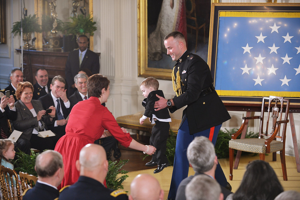 . A military aide hands Colin Romesha, the son of Medal of Honor recipient Clinton Romesha, to his mother Tammy Romesha ahead of a presentation ceremony for Clinton Romesha, in the East Room of the White House on February 11, 2013 in Washington, DC. . AFP PHOTO/Mandel NGAN/AFP/Getty Images