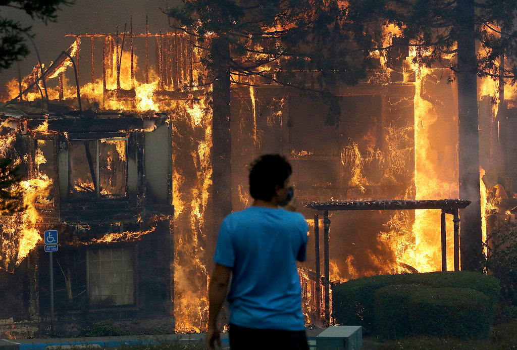 . Rudy Habibe, from Puerto Rico, stands by the burning Hilton Sonoma Wine Country hotel, where he was a guest, in Santa Rosa, Calif., Monday, Oct. 9, 2017. Wildfires whipped by powerful winds swept through Northern California, sending residents on a headlong flight to safety through smoke and flames as homes burned. (AP Photo/Jeff Chiu)