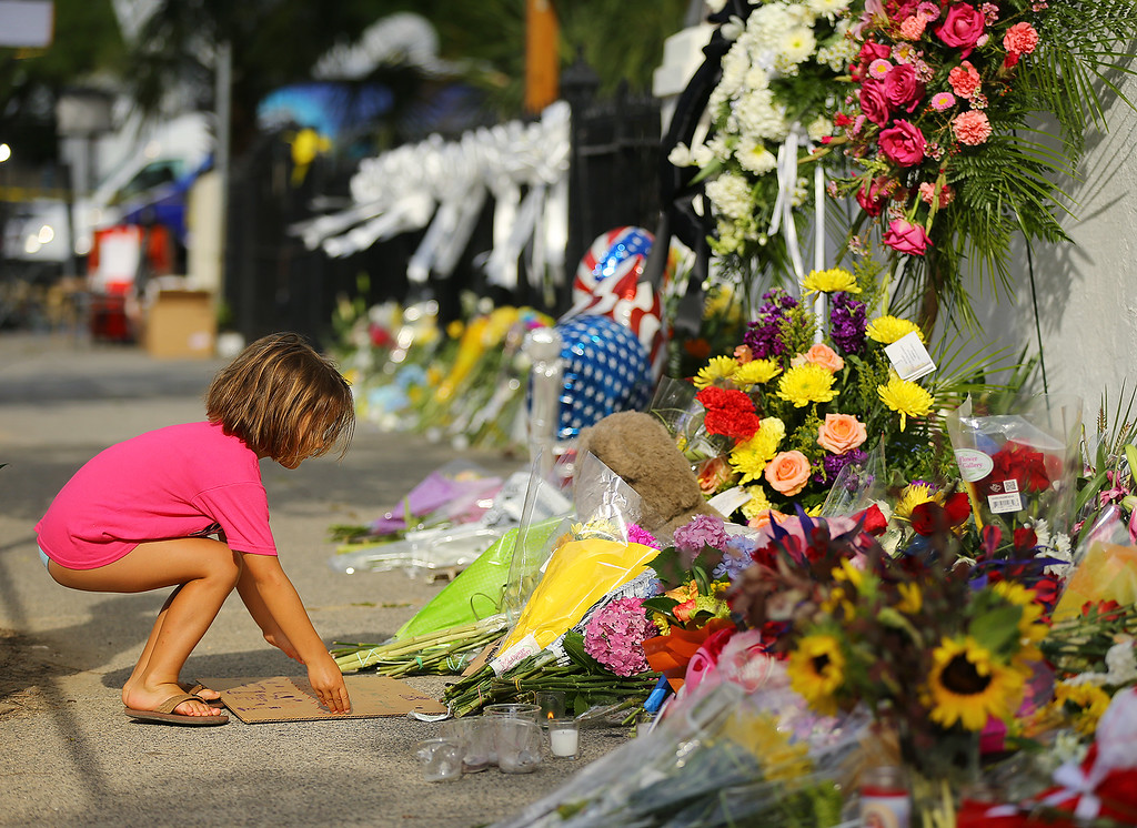 . Lydia Blessing, 4, places a hand written note at a memorial in front of the Emanuel AME Church on Friday, June 19, 2015 in Charleston, S.C.  Dylann Storm Roof, 21, is accused of killing nine people during a Wednesday night Bible study at the church.   ( Curtis Compton/Atlanta Journal-Constitution via AP)