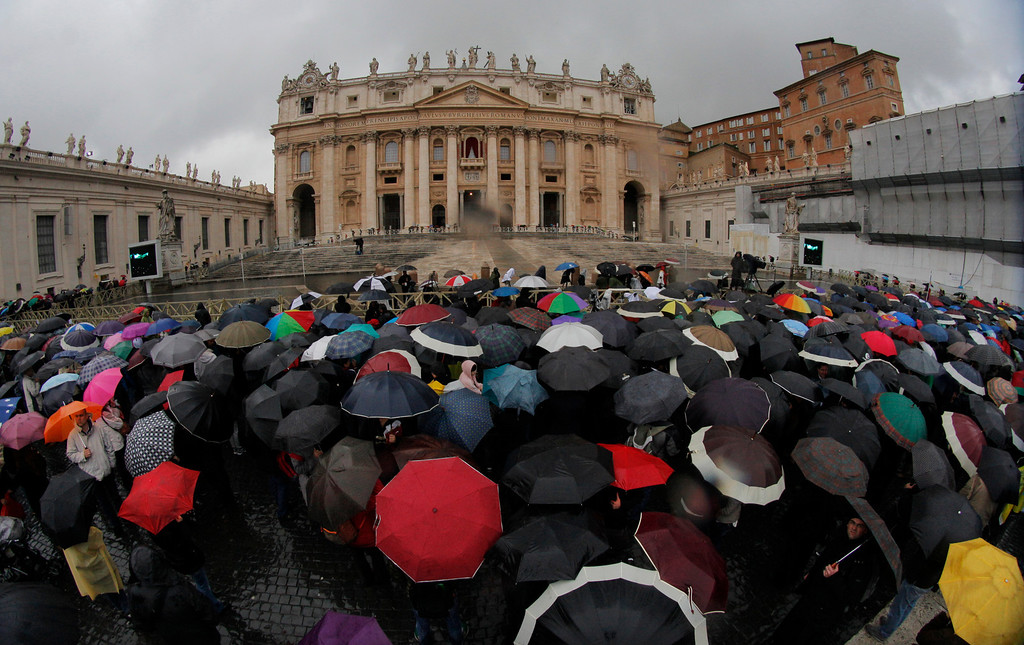. Visitors wait in front of St. Peter\'s Basilica while cardinals meet in conclave in the Sistine Chapel to elect a new pope in St. Peter\'s Square at the Vatican, Wednesday, March 13, 2013. (AP Photo/Dmitry Lovetsky)