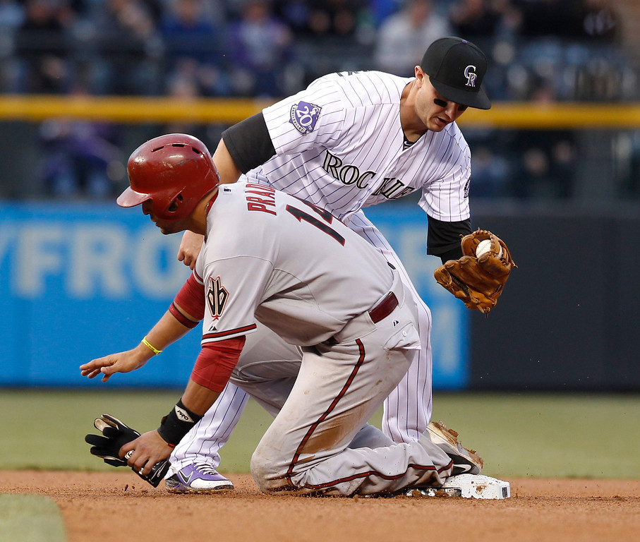 . Arizona Diamondbacks\' Martin Prado, front, is tagged out at second base by Colorado Rockies shortstop Troy Tulowitzki in the fourth inning of a baseball game in Denver on Saturday, April 20, 2013. Prado was trying to advance on a fly ball from first to second base on the play. (AP Photo/David Zalubowski)
