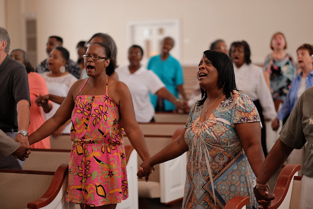 . Worshippers hold hands during a service at the Mount Moriah Baptist Church in Spartanburg, S.C. on Saturday, June 20, 2015, in honor of those shot and killed in a Charleston, S.C. church earlier in the week. (Tim Kimzey/Spartanburg Herald-Journal via AP)