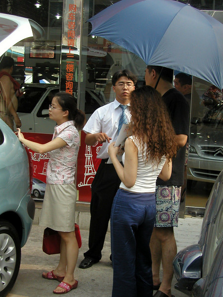 salesman discussing cars, Beijing car dealership, June 2004