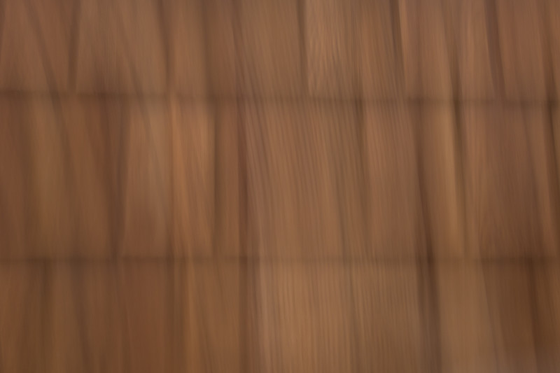 Vertical lines of cedar shakes on the side of a building are blurred in an abstract photo