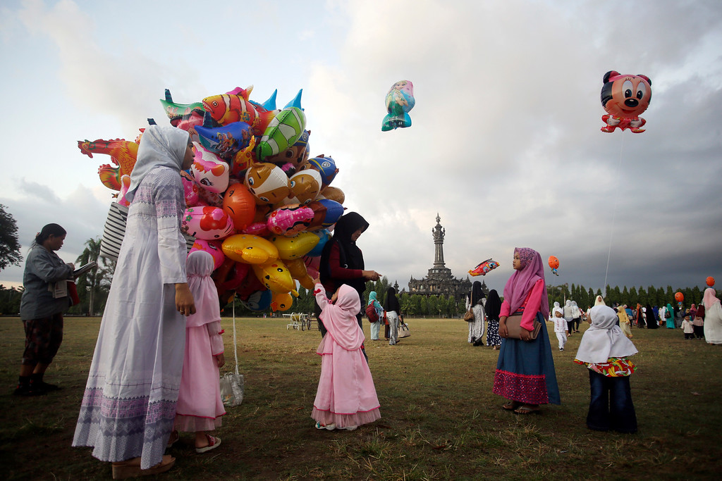 . Children get balloons as they attend Eid al-Fitr prayer sto mark the end of the holy fasting month of Ramadan in Bali, Indonesia, Friday, June 15, 2018. (AP Photo/Firdia Lisnawati)