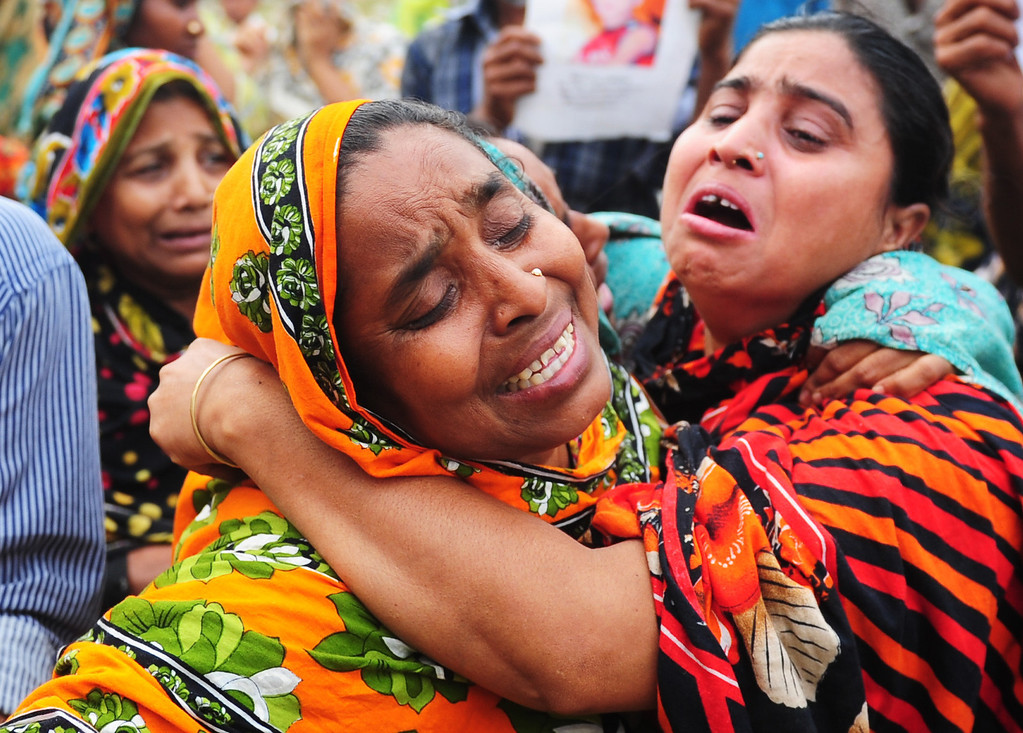 . Bangladeshi relatives of a dead worker reacts after seeing the body three days after an eight-storey building collapsed  in Savar, on the outskirts of Dhaka on April 27, 2013. Police arrested two textile bosses over a Bangladeshi factory disaster as the death toll climbed to 332 and distraught relatives lashed out at rescuers trying to detect signs of life. MUNIR UZ ZAMAN/AFP/Getty Images