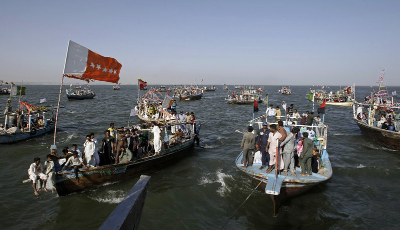 . Supporters of an independent Pakistani election candidate participate in a waterborne rally to highlight the challenges faced by their embattled fishing community in the Arabian Sea off the coast of Karachi, Pakistan on Friday, May 3, 2013. Backers of independent political candidate Haji Usman Ghani took to the water Friday on a flotilla of fishing boats in the run up to the May 11, 2013 vote which will mark the first time that a democratically elected civilian government has finished a full term and handed over power to another such government in Pakistan. (AP Photo/Fareed Khan)
