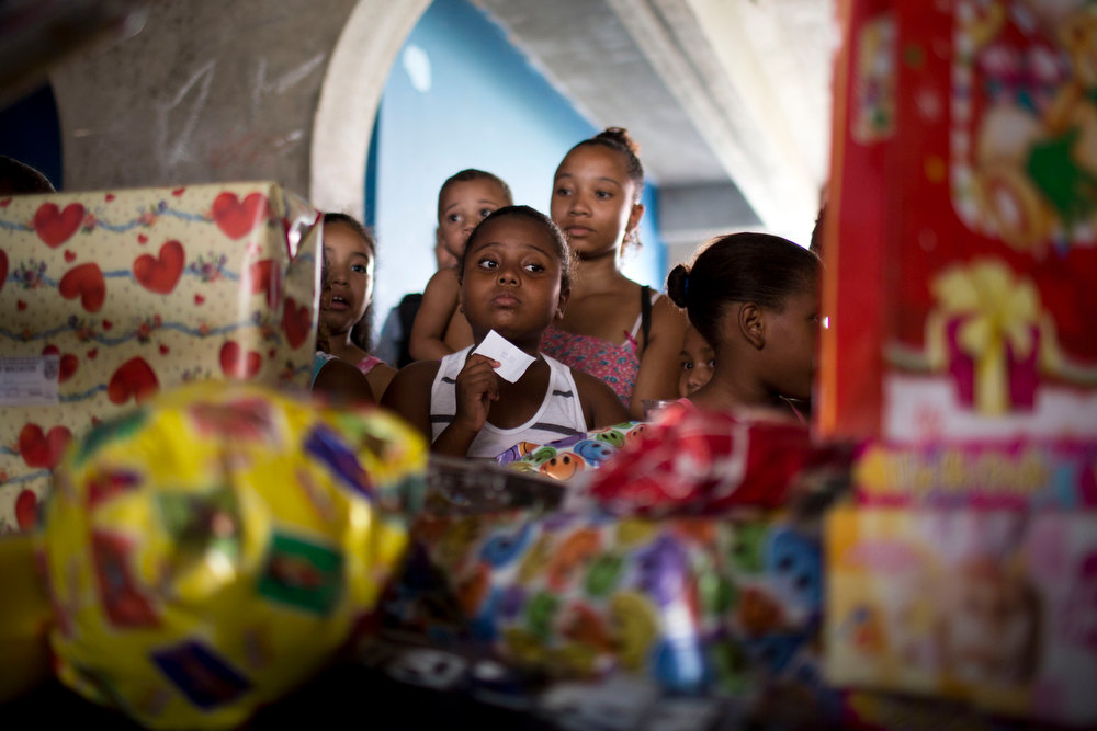 Description of . Children wait to receive gifts at a Christmas party organized by the Pacifying Police Unit, or UPP, in the Macacos slum in Rio de Janeiro, Brazil, Thursday, Dec. 20, 2012. The Pacifying Police Unit, or UPP, organized for Santa to visit the pacified slum to hand out Christmas gifts to young residents. (AP Photo/Felipe Dana)