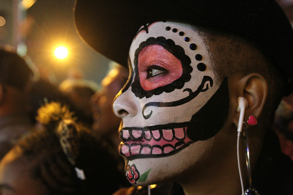 . Jocelyn Martinez, of Yonkers, N.Y., watches the Village Halloween Parade as it makes its way up New York\'s Sixth Avenue on Thursday, Oct. 31, 2013.  (AP Photo/Tina Fineberg)