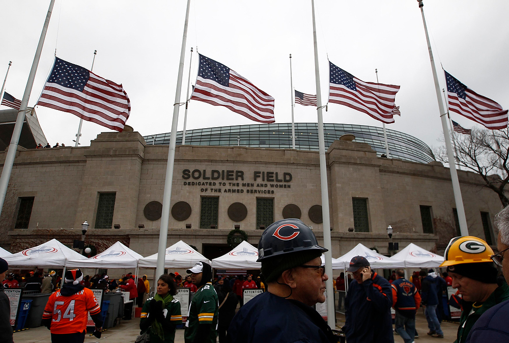 Description of . U.S. flags fly at half staff in memory of 20 children and six adults who lost their lives  in a mass shooting at Sandy Hook Elementary School, as football fans arrive for an NFL football game at Soldier Field in Chicago, December 16, 2012. REUTERS/Jim Young