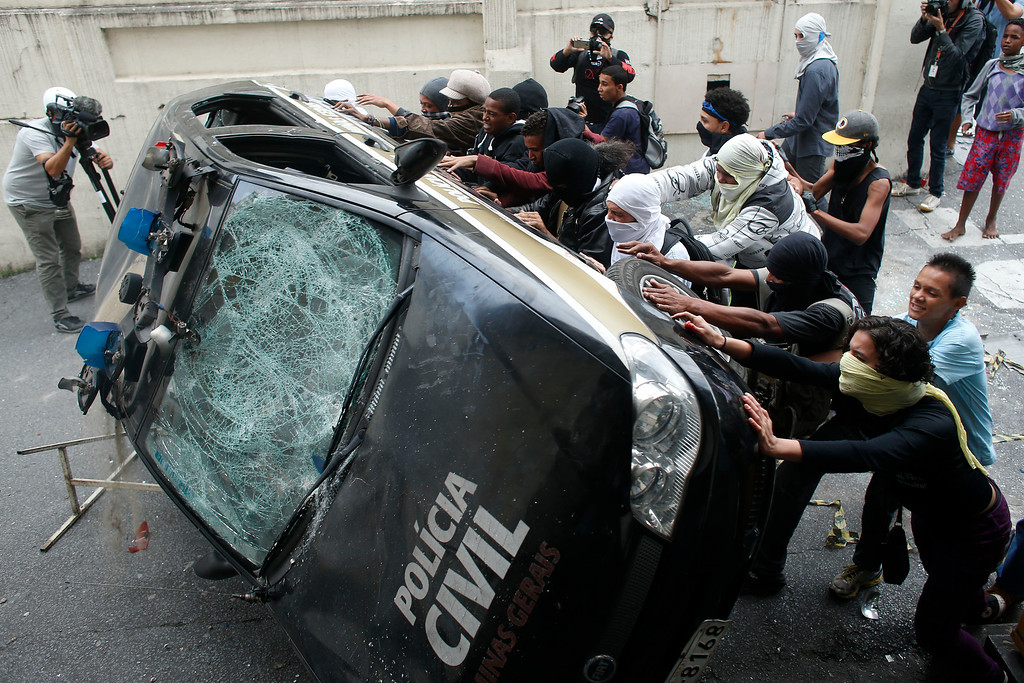 . Demonstrators push over a police car during a protest demanding better public services and against the money spent on the World Cup soccer tournament in Belo Horizonte, Brazil, Thursday, June, 12, 2014. (AP Photo/Victor R. Caivano)