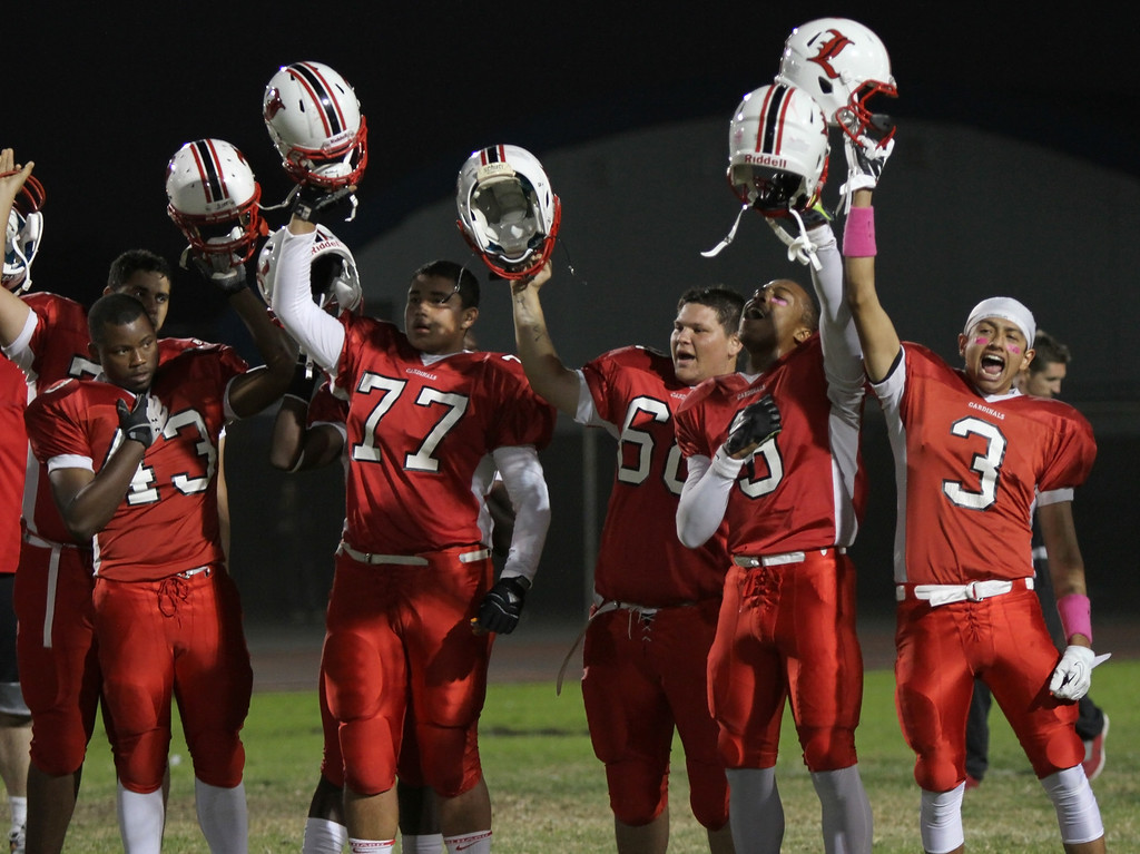 . Lawndale players raise their helmet at the conclusion of the national anthem before kickoff against El Segundo in a Pioneer League matchup at Leuzinger High School on Friday, October 11, 2013 in Lawndale, Calif.  (Michael Yanow / For the Daily Breeze)