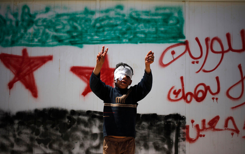 ". Syrian refugee Bashar al-Zalfi, 10, waves the victory sign while posing in front of a wall with the colors of the revolutionary flag, and Arabic reading, ""Syria, don\'t worry, we will return,\"" at Zaatari refugee camp, in Mafraq, Jordan, Thursday, April 25, 2013. Bashar was injured with his right eye in Daraa, Syria during a bombing by the government Syrian forces.  (AP Photo/Mohammad Hannon)"
