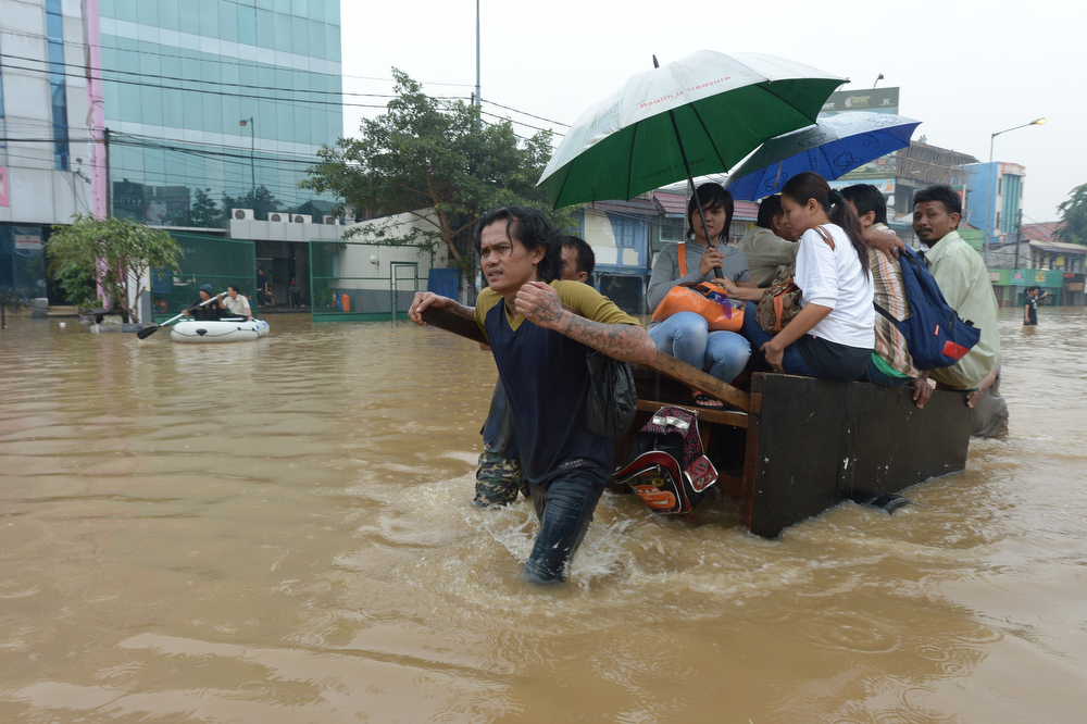 . People ride a man pulled cart through a flooded street in Jakarta on January 16, 2013. Floodwaters have inundated 52 subdistricts in Jakarta, claiming one life and displacing some 6,000 residents, according to the National Disaster Mitigation Agency (BNPB). ADEK BERRY/AFP/Getty Images