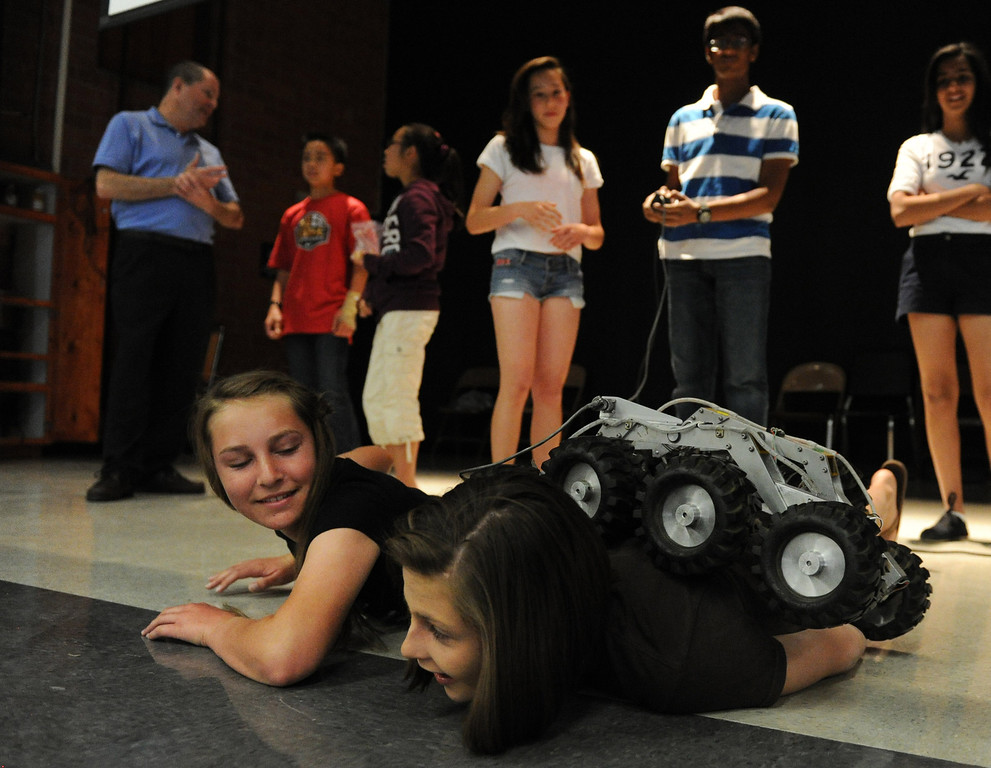 . (John Valenzuela/Staff Photographer)   Eighter grader Tiffiany Renken (left) watches as Anee Patnam controls a small robotic rover as it drive over Ciera Hammond (left) and Maddie Palmer (right) at Cope Middle School in Redlands, Friday , April 19, 2013.  Brian Cooper, lead rover driver of Curiosity and the worlds first Mars rover driver, spoke to eight graders at the middle school about his mulitple missions to Mars.
