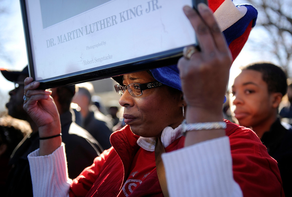 . The Martin Luther King Jr. Marade started at City Park and finished downtown. Lisa Ward of Denver holds aloft a portrait of King as she listens to speakers at the MLK statue in City Park  before the start of the march/parade on Monday, January 21, 2013.   (Photo By Cyrus McCrimmon / The Denver Post)