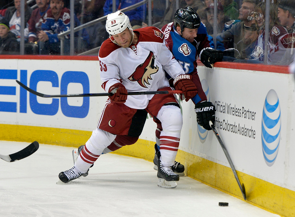 . Phoenix Coyotes defenseman Derek Morris (53) and Colorado Avalanche left wing Cody McLeod (55) go after the puck during the first period of an NHL hockey game on Friday, Feb. 28, 2014, in Denver. (AP Photo/Jack Dempsey)