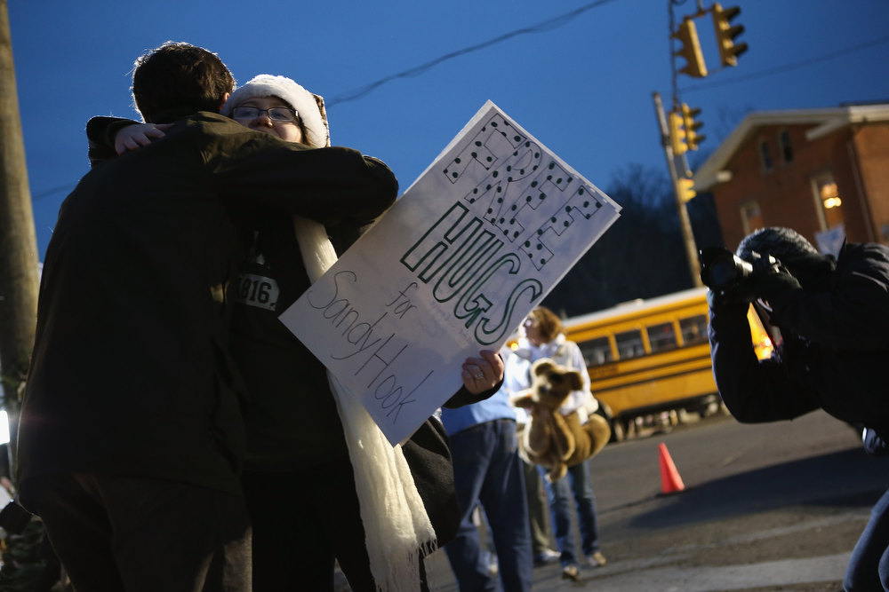 Description of . Mourners embrace at a memorial for massacre victims on December 20, 2012 in Newtown, Connecticut. Six funeral services were held Thursday for students and teachers in the Newtown area.  (Photo by John Moore/Getty Images)
