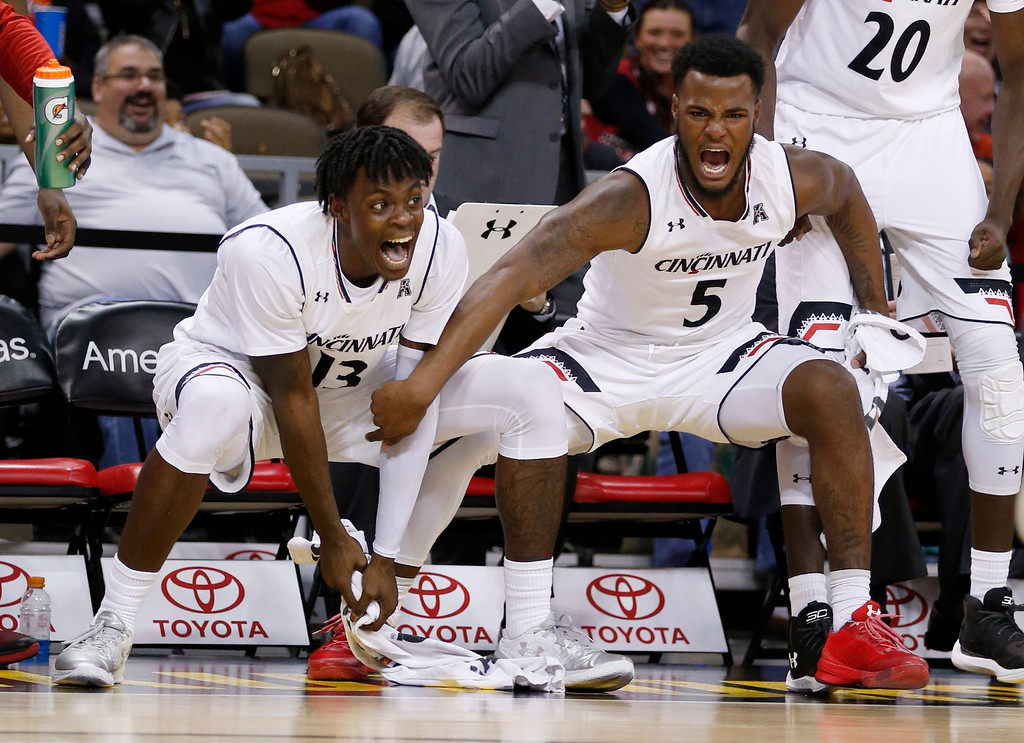 . Cincinnati forward Trevon Scott, left, and guard Trevor Moore (5) celebrate a teammate\'s dunk during the second half of an NCAA college basketball game against Cleveland State, Thursday, Dec. 21, 2017, in Highland Heights, Ky. Cincinnati won 81-62. (AP Photo/Gary Landers)