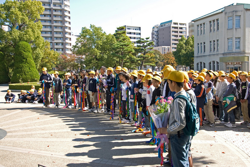 Children carrying offerings in front of Children's memorial in Peace Park - Hiroshima, Japan