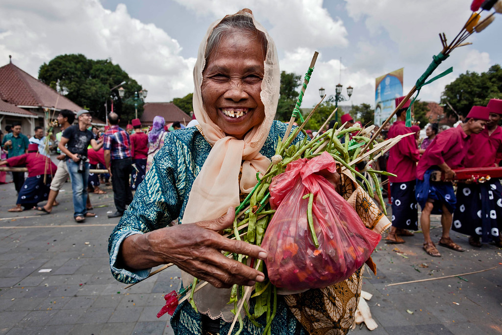 . YOGYAKARTA, INDONESIA - AUGUST 08:  A Javanese elderly woman holds vegetables from the \'Gunungan Lanang\' during the Grebeg Syawal ceremony on August 8, 2013 in Yogyakarta, Indonesia. Grebeg Syawal is a tradition that follows the holy month of Ramadan to welcome Eid Al-Fitr. The tradition involves an offering of vegetables, peppers, eggs, and other items, called \'Gunungan Wadon\' and \'Gunungan Lanang\' which are brought to the Grand Mosque as part of a symbol of alms from Sri Sultan Hamengkubuwono X to his people. Receiving part of the Gunungan is believed to be good luck and a blessing for the year ahead. (Photo by Ulet Ifansasti/Getty Images)