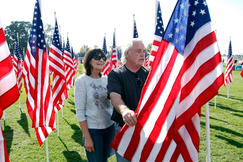 . U.S. Navy Veteran, Ronald Ray Bergstrom and his wife Sharon Bergstrom, of LA Verne, stand next to the flag dedicated him, during the opening ceremony for the Field of Valor, where 2,027 flags are posted in honor of Veterans Day, at the Field of Valor at Sierra Vista Middle School in Covina, CA., Sunday, November 10, 2013. (Photo by James Carbone for the San Gabriel Valley Tribune)