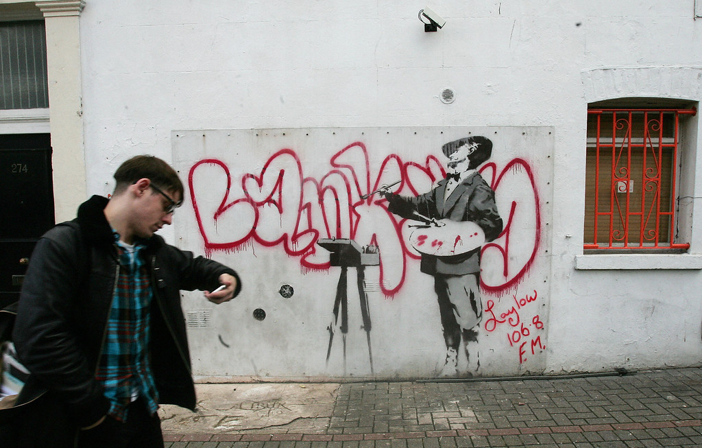 . A man walks past a graffiti mural by British artist Banksy, spraypainted on a wall on Portobello road in London, 14 January 2008. The wall has been put up for bid on the internet auction site Ebay. The successful bidder must also cover the cost of the wall\'s removal and delivery. The wall has reached a price of 1,000,000 GBP. (CARL DE SOUZA/AFP/Getty Images)