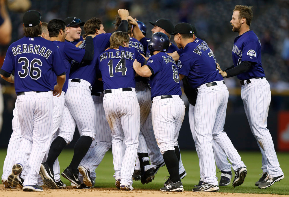. Members of the Colorado Rockies mob Charlie Blackmon after his walkoff, RBI-single against the San Francisco Giants in the ninth inning of the Rockies\' 10-9 victory in a baseball game in Denver on Monday, Sept. 1, 2014. (AP Photo/David Zalubowski)
