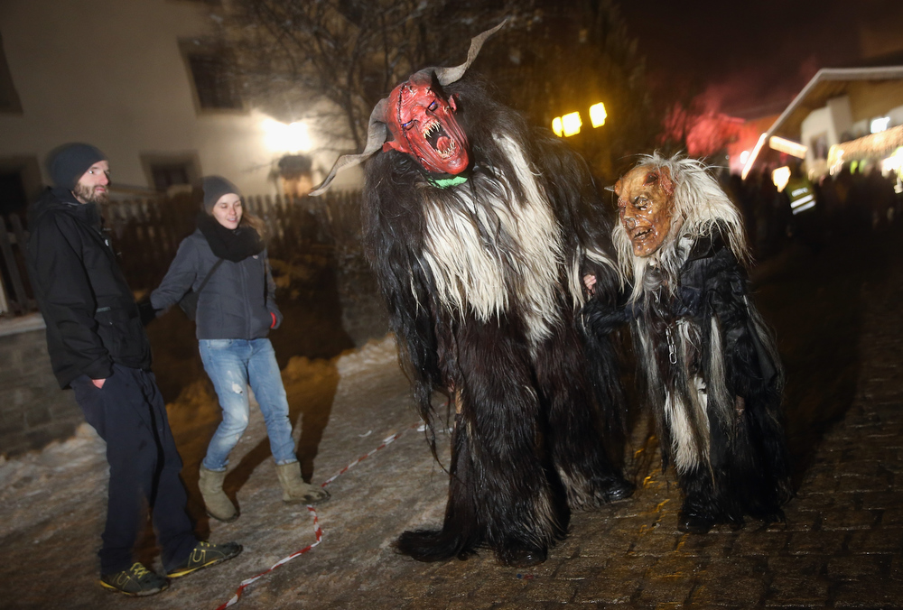 . Participants dressed as adult and child Krampus creatures walk past onlookers whilst in search of delinquent children during Krampus night on November 30, 2013 in Neustift im Stubaital, Austria. Sixteen Krampus groups including over 200 Krampuses participated in the first annual Neustift event. Krampus, in Tyrol also called Tuifl, is a demon-like creature represented by a fearsome, hand-carved wooden mask with animal horns, a suit made from sheep or goat skin and large cow bells attached to the waist that the wearer rings by running or shaking his hips up and down. Krampus has been a part of Central European, alpine folklore going back at least a millennium, and since the 17th-century Krampus traditionally accompanies St. Nicholas and angels on the evening of December 5 to visit households to reward children that have been good while reprimanding those who have not. However, in the last few decades Tyrol in particular has seen the founding of numerous village Krampus associations with up to 100 members each and who parade without St. Nicholas at Krampus events throughout November and early December.  (Photo by Sean Gallup/Getty Images)