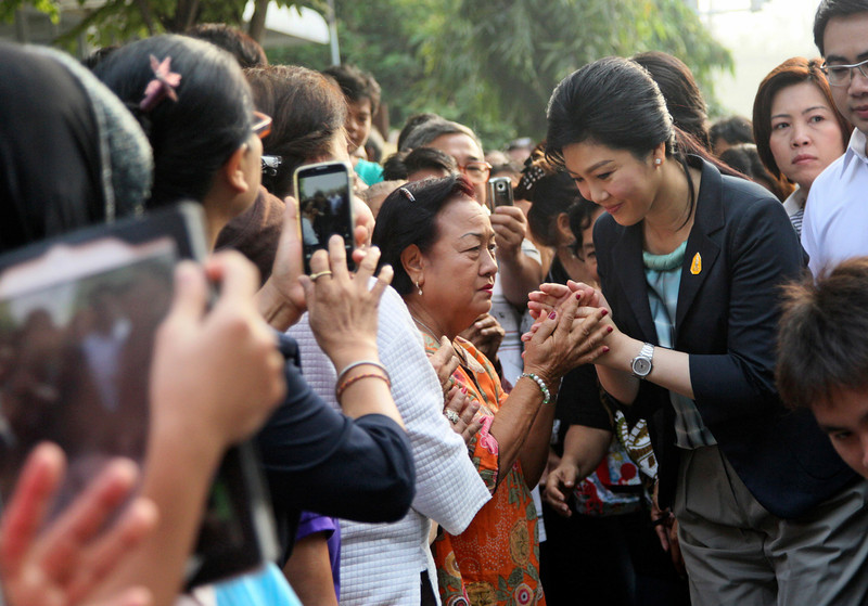 . Thai Prime Minister Yingluck Shinawatra, right, greets her supporters as she arrived at a polling station to cast her ballot for the general election in Bangkok, Thailand, Sunday, Feb. 2, 2014. Thailand\'s tense national election got underway Sunday amid signs of disruptions at several polling stations and fears of violence, a day after gun battles between protesters and would-be voters broke out at a busy Bangkok intersection. (AP Photo/Sakchai Lalit)